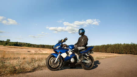 Biker man on a motorcycle in a leather jacket and helmet looks at the road