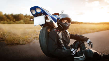 Motorcyclist or biker in a black leather jacket and a protective helmet sits near a stylish sports motorcycle on the asphalt road Фото со стока