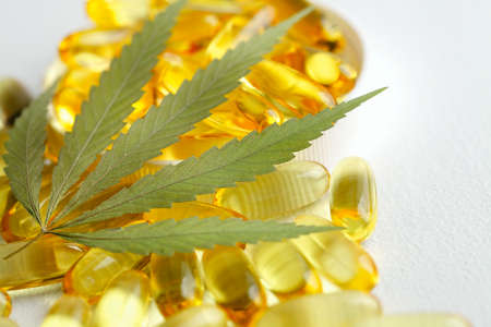 Cannabis CBD capsules are a medical cannabis product with leaves, CBD hemp oil capsules, on white background with copy space