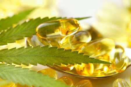 Medical cannabis products, leaf, capsules and CBD oil on white background. Pharmaceutical gelatin softgels with biological plant herbal. Organic dietary supplements concept