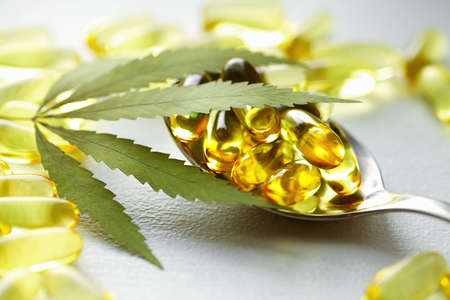 Cannabis essential oil capsules on white background. CBD oil capsules and hemp leaves