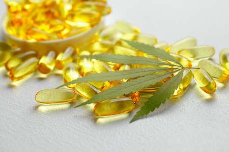 CBD oil capsules and hemp leaves. Macro close up of capsules of biological and ecological hemp plant herbal pharmaceutical cbd oil