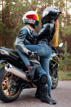 Motorcyclist in leather jacket and helmet stands next to sports motorcycle and hugged girl in helmet and tilted her, blurred background