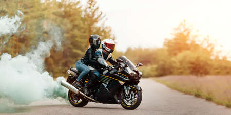 Motorcyclist in protective gear and helmet sitting with a girl on a sports motorcycle on a blurred background with smoke, copy space