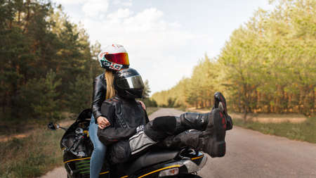 Girl and guy motorcyclist on a sports motorcycle in helmets sitting together and hugging on a blurred background with copy space 免版税图像