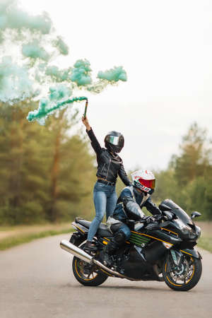 Motorcyclist in leather jacket and helmet sits on sports motorcycle, girl stands, blurred background with smoke, copy space 免版税图像
