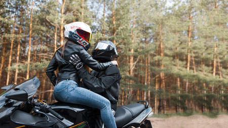 Girl and guy on a sports motorcycle in helmets sitting together and hugging on a blurred background with copy space
