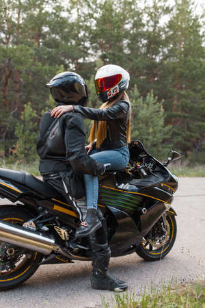 Motorcyclist in leather outfit sits with a girl on a motorcycle in helmets and hugs against the background of trees in the forest