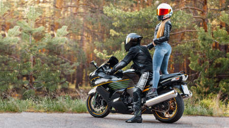 Motorcyclist in a leather jacket sits on a motorcycle and a girl stands on a motorcycle in helmets against the background of trees in the forest