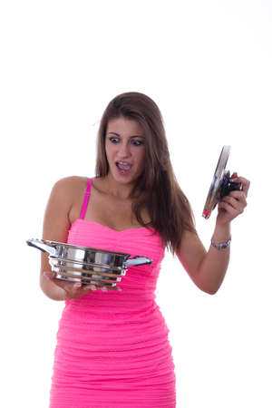 inexperienced: beautiful girl holding a pot in her hand with reaction as a consequence of  inexperienced cooking Stock Photo