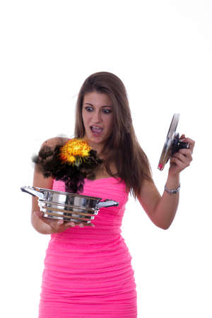 consequence: beautiful girl holding a pot in her hand with reaction as a consequence of terrible cooking Stock Photo