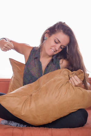 beautiful angry woman sitting on couch and punching the pillow Stock Photo