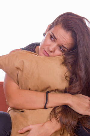cute sad girl sitting and hugging pillow photo