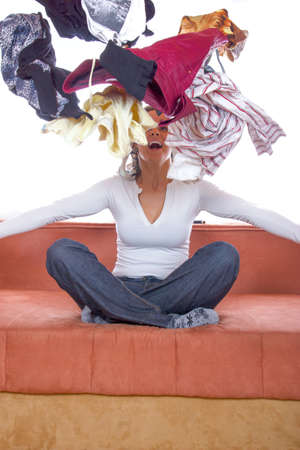 disorganization: cheerful girl sitting and throwing clothes in the air Stock Photo