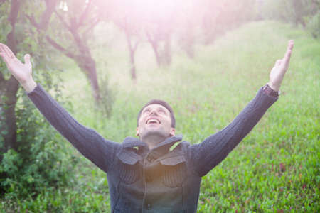 young man with open arms looking up