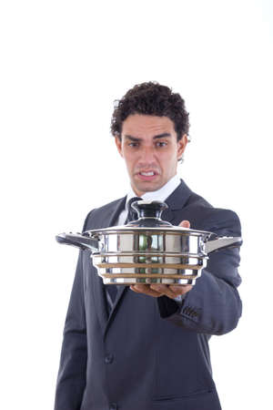 man in suit looking at pot for cooking with expression photo