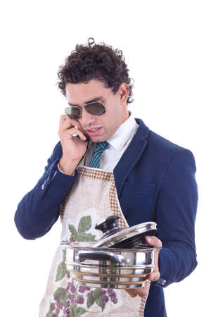 man in suit with an apron holding a cooking pot and talking over phone photo