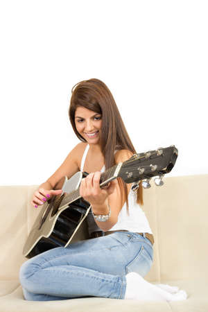 pretty brunette girl in white shirt and jeans playing guitar on the sofa Reklamní fotografie