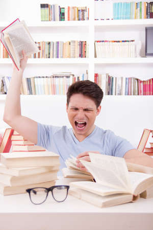 angry student  surrounded by books  throws a book  in his room photo
