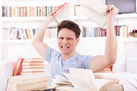 unwillingness: angry student  surrounded by books  throws books  in his room Stock Photo