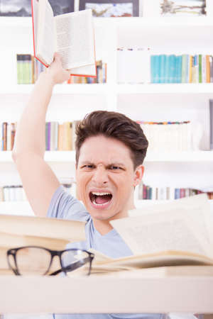 upset and  angry student with expression surrounded by books  throwing a book photo
