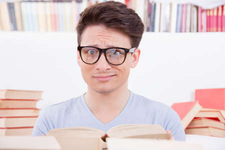 confused student wtih glasses and blue t-shirt surrounded by books Stock Photo