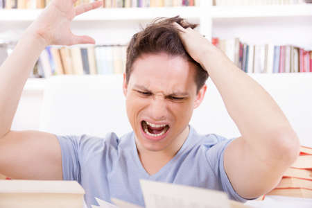 unwillingness: dissatisfied and upset student with hand on his head surrounded by books