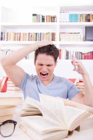 unwillingness: dissatisfied and upset student i blue t-shirt with hand on his head surrounded by books Stock Photo