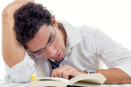 sleepy and tired adult man with glasses in white shirt and tie sitting with book photo