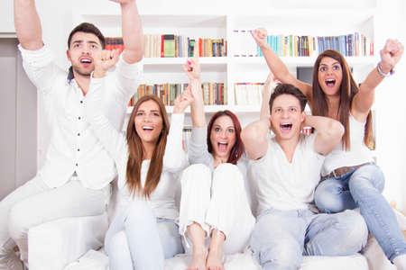 mujer viendo tv: alegres amigos emocionados viendo el partido de fútbol en la televisión