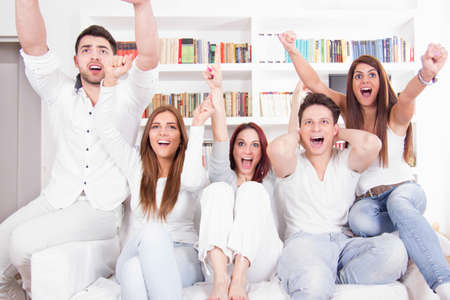 telly: excited cheerful friends watching football game on tv