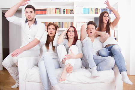 group of friends watching bad game on tv with expression because their team lost photo