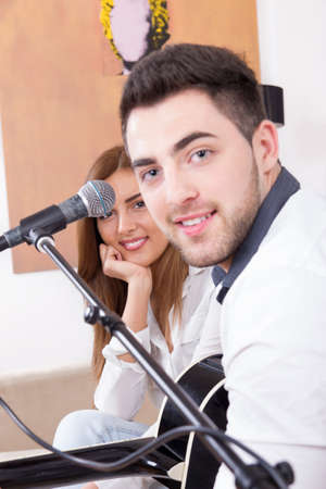 man in white shirt playing guitar and singing to a cute girl photo