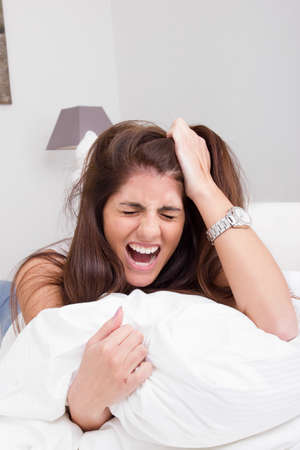 pissed: beautiful young angry woman on the bed pulling her hair and screaming Stock Photo