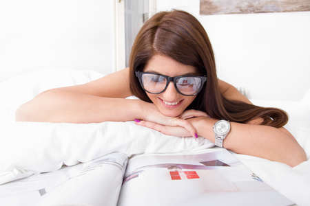 pretty young woman reading papers lying on the bed wearing glasses photo