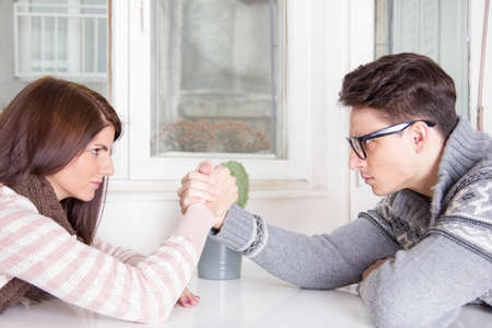 arm wrestling challenge between a young couple at home Фото со стока
