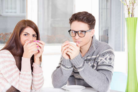 young couple holding cups of coffee in hands drinking it at home photo