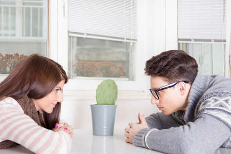 couple staring at each other across the table at home photo