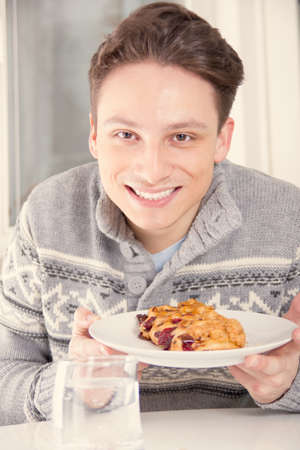 young smiling man holding dessert on the plate, warm effect photo