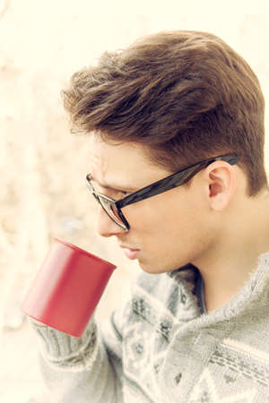 young man with glasses drinking coffee outdoors, vintage effect photo