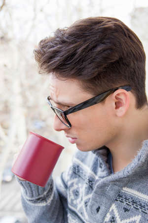 young man with glasses drinking coffee outdoors photo