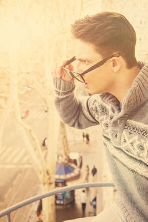 young surprised man with glasses and cup of coffee in his hand standing on the balcony, vintage effect photo