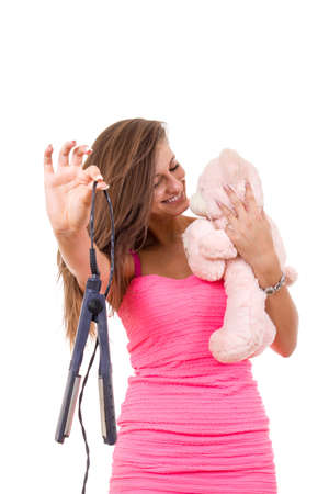 beautiful young woman refuses to grow up holding teddy bear disclaiming hair straightener photo
