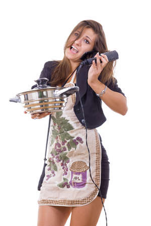 clumsy: beautiful inexperienced female cook trying to be housewife talking on the phone Stock Photo