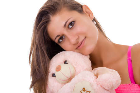 pretty young woman holding teddy bear reminding her of childhood photo