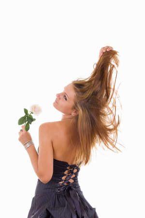 looked: pretty girl in black dress with turn back holding a white rose, studio isolated on white background