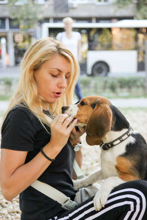beautiful young woman holding and feeding beagle puppy dog photo