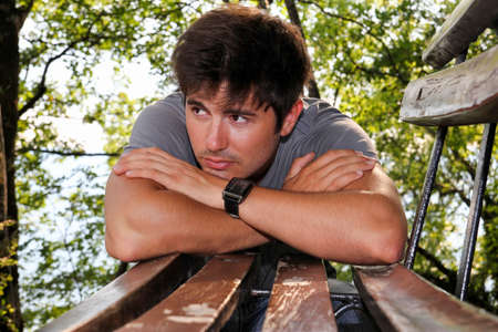 handsome young man leaning on a bench in the park photo