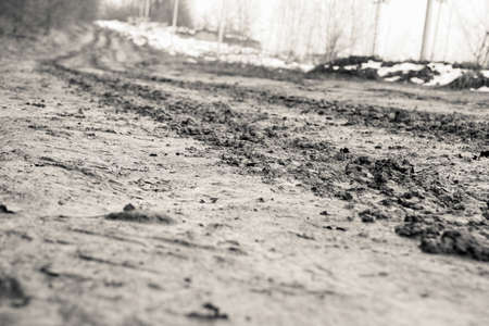 rural road with mud and tire tracks in black and white style photo