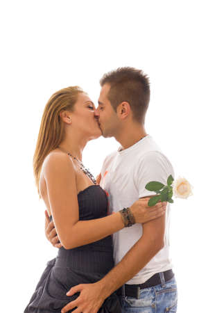sweet couple in love kissing in embrace with rose in girls hand photo